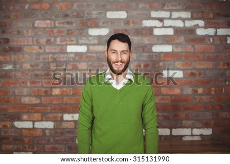 Portrait of happy businessman standing against brick wall - stock photo