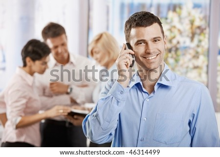 Portrait of happy businessman talking on mobile phone in office, smiling. - stock photo