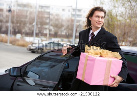 Portrait of happy businessman walking out of his car with big giftbox in hand