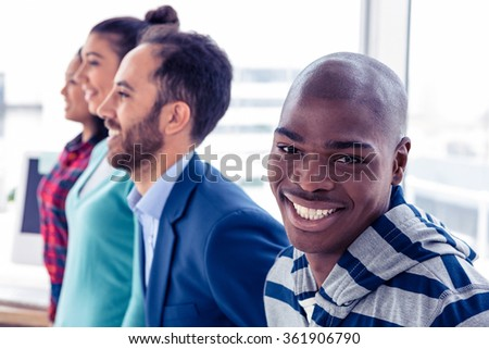 Portrait of happy businessman with colleagues standing in creative office