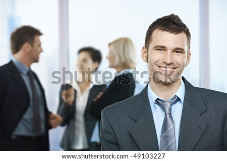 Portrait of happy businessman with coworkers talking in the background. - stock photo