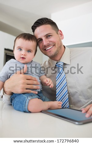 Portrait of happy businessman with digital tablet holding babyv in house