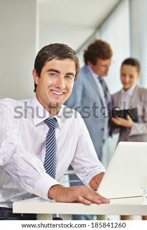 Portrait of happy businessman with two colleagues interacting on background - stock photo
