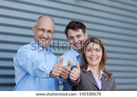 Portrait of happy businessmen and businesswoman gesturing thumbs up against shutter - stock photo
