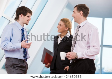 Portrait of happy businesspeople speaking to each other at break