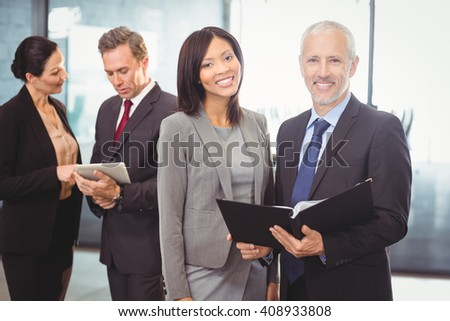 Portrait of happy businesspeople with a file and colleagues standing behind using laptop - stock photo