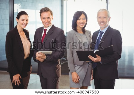 Portrait of happy businesspeople with file and digital tablet in office