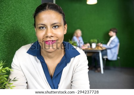 Portrait of happy businesswoman at office lobby with colleagues in background