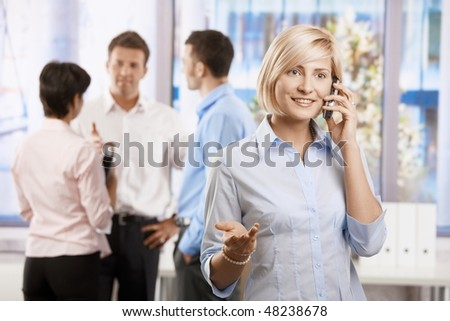 Portrait of happy businesswoman calling in office, smiling. - stock photo