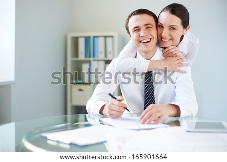 Portrait of happy businesswoman embracing her colleague in office and both looking at camera - stock photo