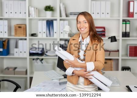 Portrait of happy businesswoman holding blueprints at office desk - stock photo
