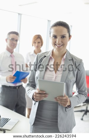 Portrait of happy businesswoman holding digital tablet with colleagues in background at office - stock photo