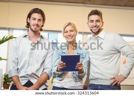 Portrait of happy businesswoman holding laptop standing with male colleagues in creative office - stock photo