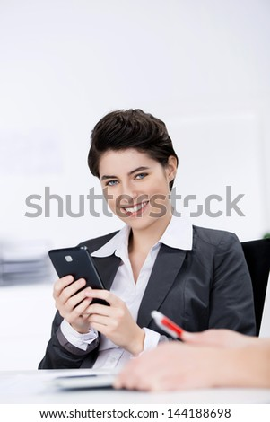 Portrait of happy businesswoman holding mobile phone with coworker in foreground at desk in office - stock photo