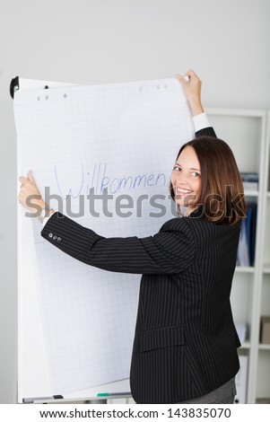 Portrait of happy businesswoman holding welcome sign in office - stock photo