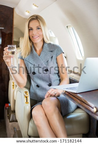 Portrait of happy businesswoman holding wineglass in private jet - stock photo