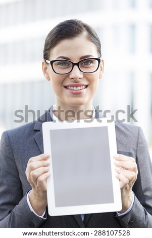 Portrait of happy businesswoman showing digital tablet outdoors