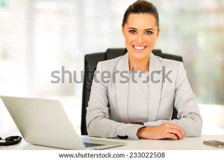 portrait of happy businesswoman sitting in office - stock photo