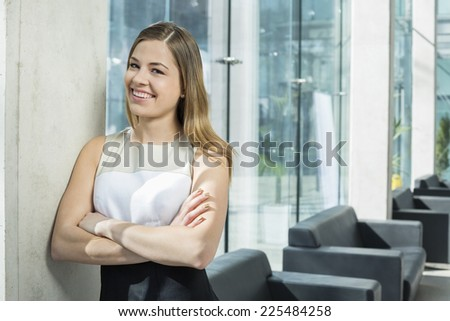 Portrait of happy businesswoman standing arms crossed at office lobby - stock photo