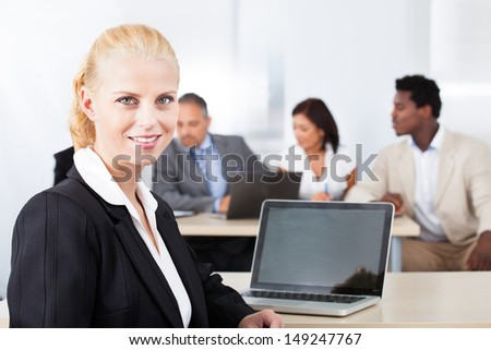 Portrait Of Happy Businesswoman Standing In Front Of Colleagues