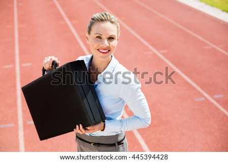 Portrait of happy businesswoman standing on running track with briefcase
