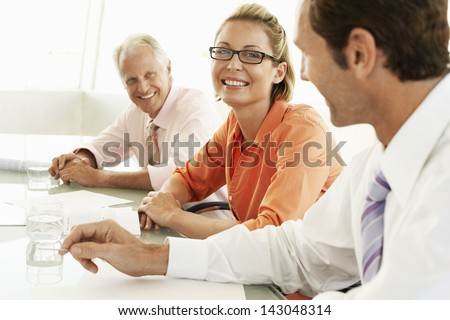 Portrait of happy businesswoman with colleagues in conference room - stock photo