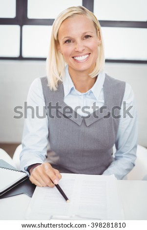 Portrait of happy businesswoman with documents sitting at desk in office - stock photo