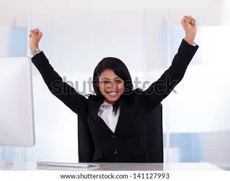 Portrait Of Happy Businesswoman With Hand Raised