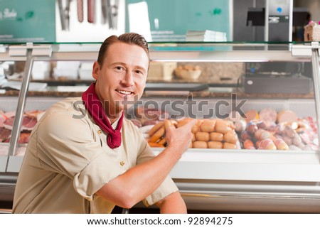 Portrait of happy butcher pointing at meat kept for selling in shop