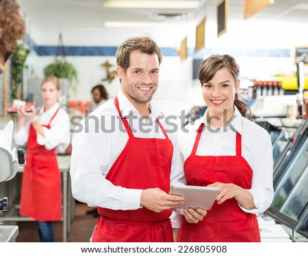 Portrait of happy butchers with digital tablet standing together in store - stock photo