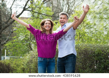 Portrait Of Happy Carefree Couple Enjoying In Park - stock photo