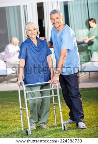 Portrait of happy caretaker helping senior woman to use Zimmer frame at nursing home lawn - stock photo