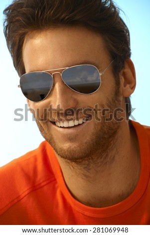 Portrait of happy casual handsome caucasian stubbly man wearing sunglasses, mirror shades, aviators. Smiling, perfect teeth. - stock photo