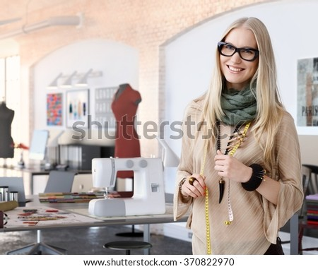Portrait of happy casual trendy caucasian blonde fashion designer businesswoman at studio. Smiling, standing, looking at camera.