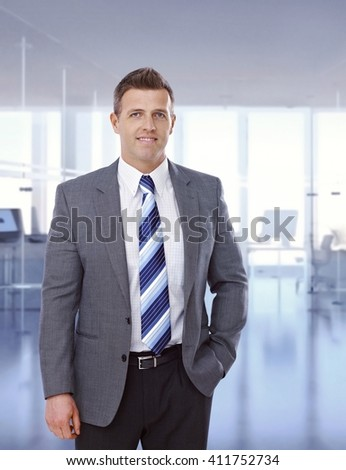 Portrait of happy caucasian businessman standing at business office, suit and tie, hands in pocket, smiling, looking at camera, copyspace. - stock photo