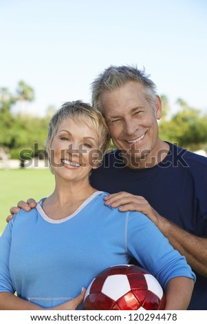 Portrait of happy Caucasian couple with football in the park - stock photo