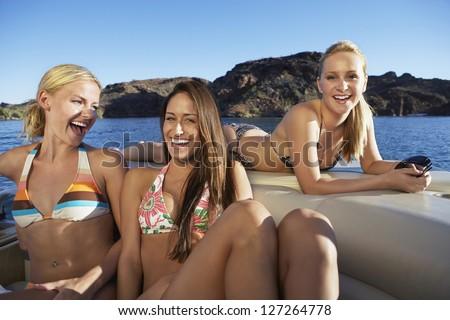 Portrait of happy caucasian female friends in boat - stock photo