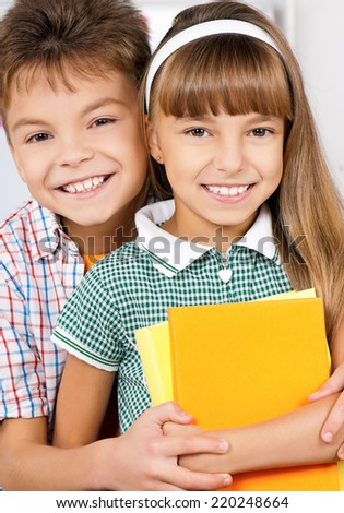 Portrait of happy caucasian friends - boy and girl, hugging in the classroom, back to school. Looking at camera. - stock photo