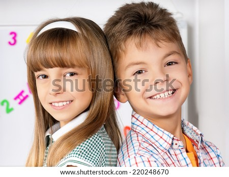 Portrait of happy caucasian friends - boy and girl, in the classroom, back to school. Looking at camera. - stock photo