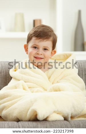 Portrait of happy caucasian kid sitting in oversize bathrobe after taking bath. Smiling, looking at camera, home indoor sofa. - stock photo