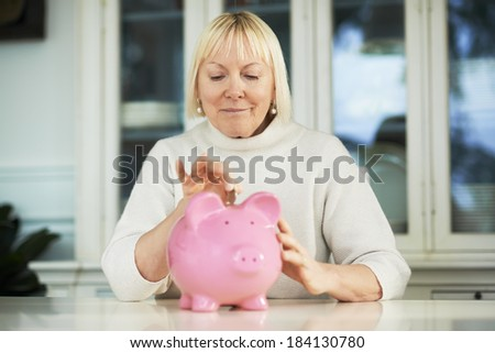 portrait of happy caucasian senior woman saving euro coin into piggybank and smiling - stock photo