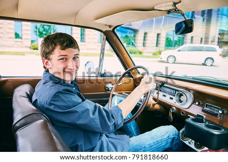 Portrait of happy Caucasian teenage boy driving car, looking at camera and smiling