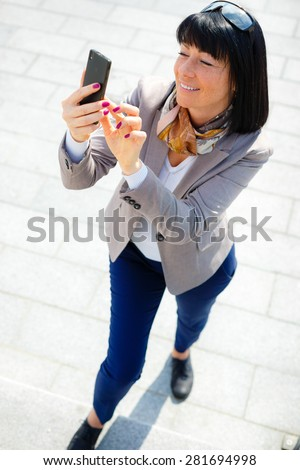 Portrait of Happy, cheerful and smile, brunette business woman, excited by what she sees on cell phone, Facial expression, reaction. Business woman sending text message from her mobile - stock photo