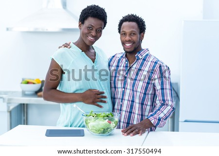 Portrait of happy cheerful couple standing in kitchen