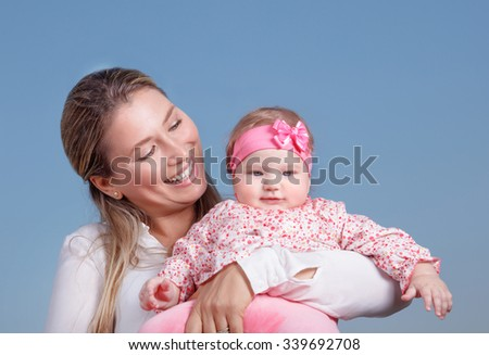 Portrait of happy cheerful mother holding on hand cute little daughter isolated on blue background, loving young family - stock photo