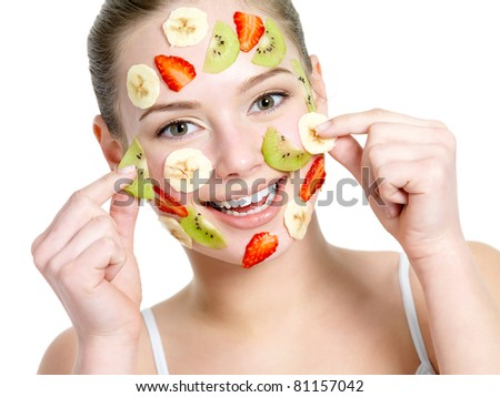 Portrait of happy cheerful young beautiful woman with fruit facial mask - isolated on white - stock photo