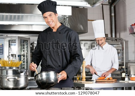 Portrait of happy chef cooking food with colleague chopping carrot in background