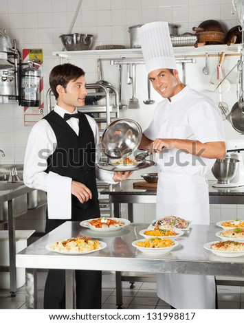 Portrait of happy chef giving pasta dish to waiter in restaurant kitchen