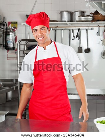Portrait of happy chef standing in commercial kitchen - stock photo