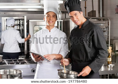 Portrait of happy chefs with digital tablet cooking in industrial kitchen